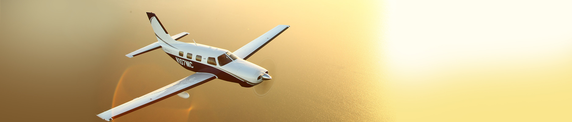 Plane flying above golden ocean